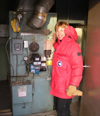Carol Fey checking a furnace.  Carol's expertise is in heating and air conditioning, as well as wiring and circuits.